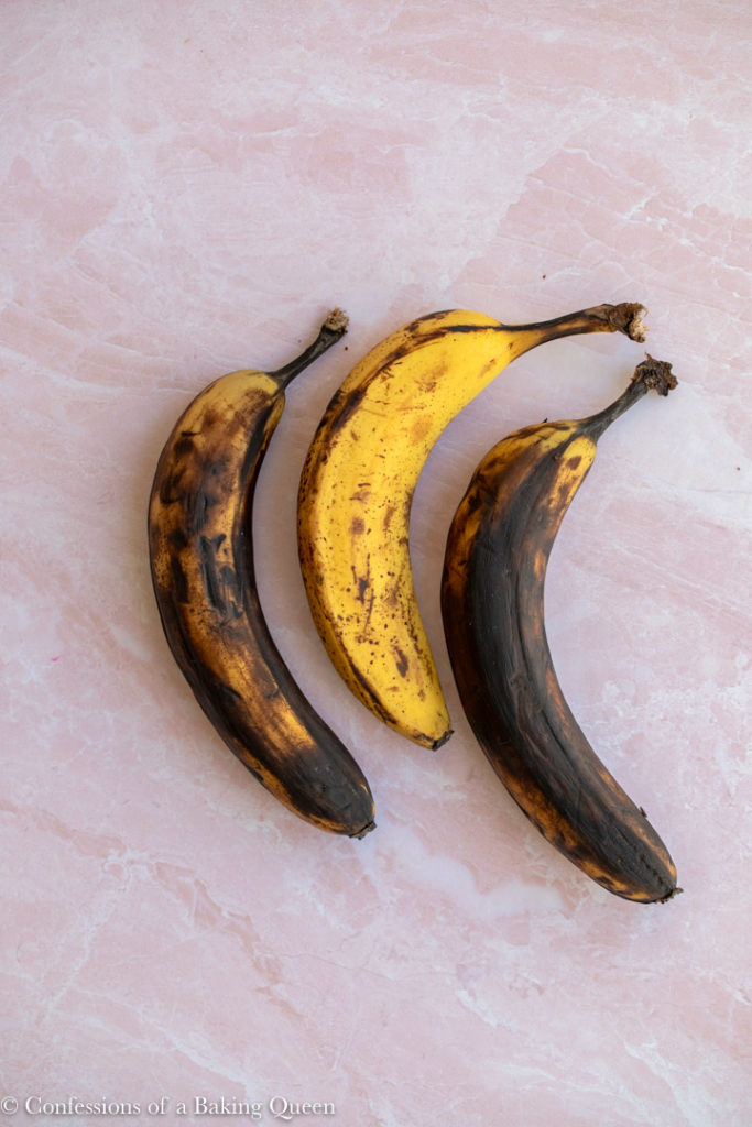 three ripe bananas on a pink background
