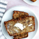 banana bread slices on a white plate with butte melting on the bread