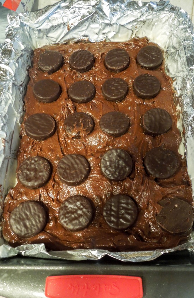 peppermint patty stuffed brownies batter in a foil lined baking pan with pattys on top