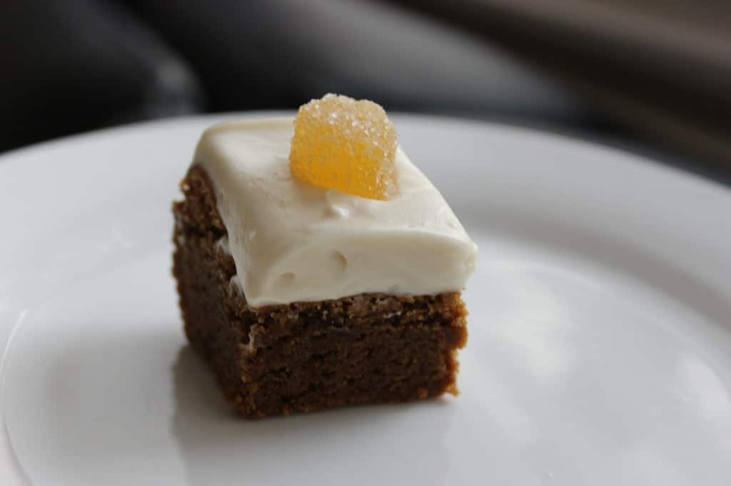 Gingerbread Brownies w/ Cream Cheese Frosting on a white plate with a black background