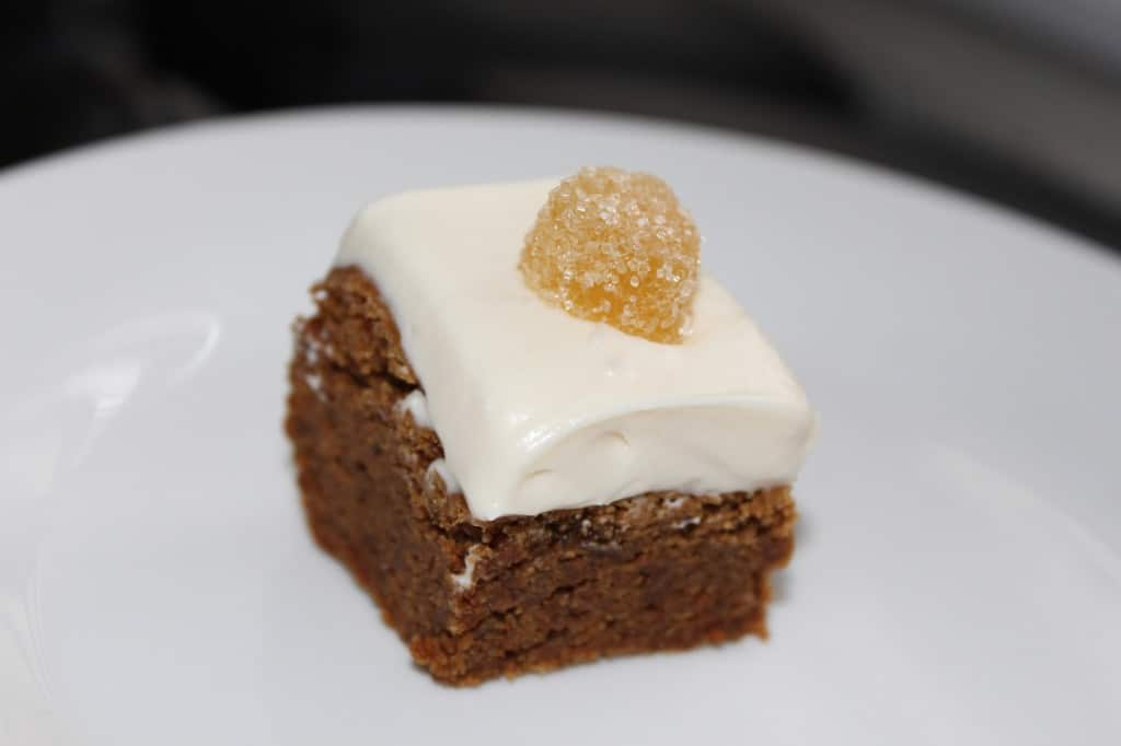 chewy gingerbread brownies topped with a cream cheese frosting and candied ginger on a white plate