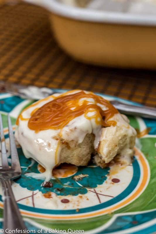 Salted Caramel Apple Cinnamon Rolls baked and frosted and drizzled with salted caramel on a blue and green plate