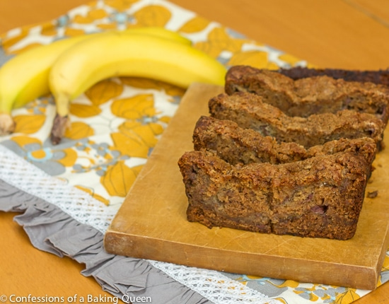 Pudding Banana Bread sliced on a wood board on a grey and yellow tea towel with bananas on