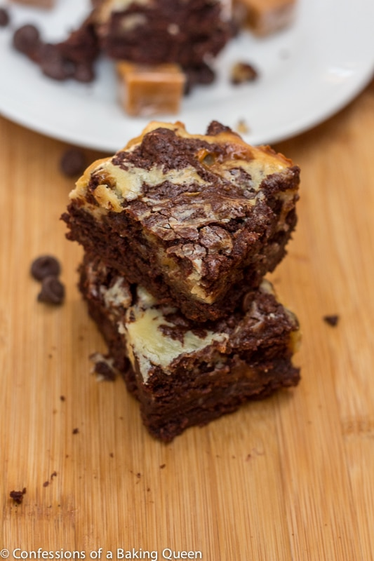 caramel cheesecake brownies stacked on top of each other on a wood board