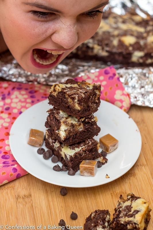 girl about to eat a stack of caramel cheesecake brownies on a white plate