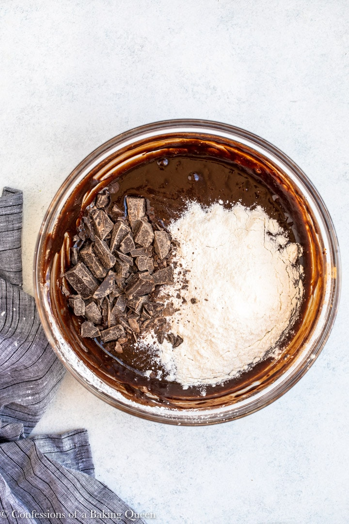 flour and chocolate chunks added to a bowl of brownie batter