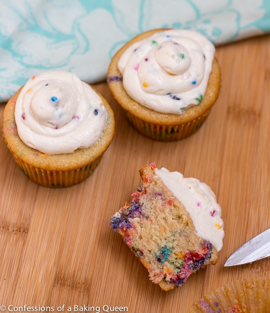 Homemade Rainbow Chip Cupcake half with two full cupcakes behind