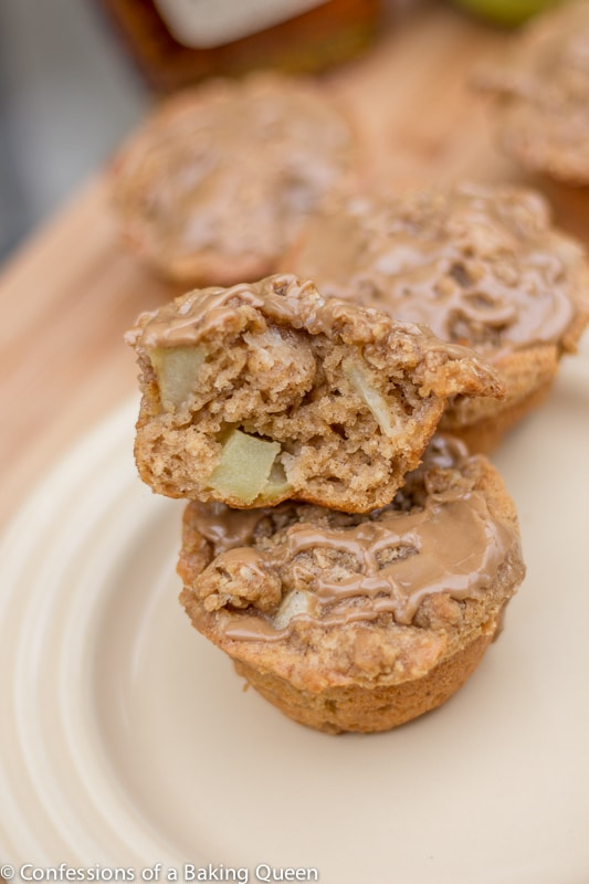 Apple Muffins with Maple Glaze stacked on top of each other one open showing inside of muffin on a cream plate
