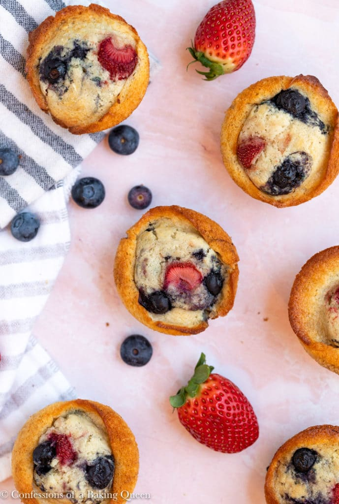 strawberry blueberry muffins on a pink surface