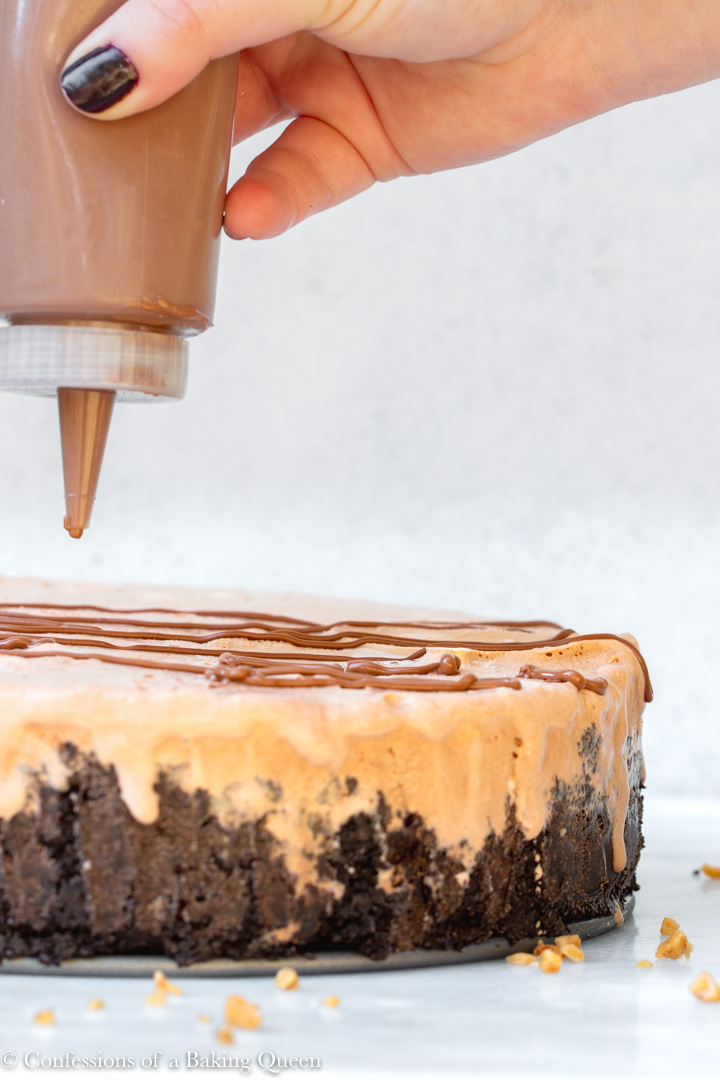 melted chocolate in a squeezy bottle drizzling chocolate on top of a baileys double chocolate ice cream cake recipe