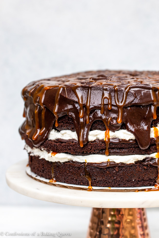 salted caramel chocolate cake served on a white marble cake stand with a copper stand