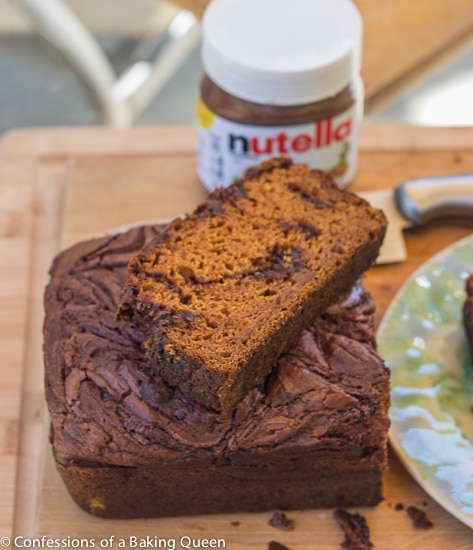 Nutella Swirled Pumpkin Bread loaf on a wood board with a piece sliced and sitting on top of it