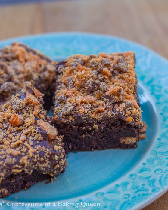 butterfinger brownies three pieces on a blue plate on a wood surface