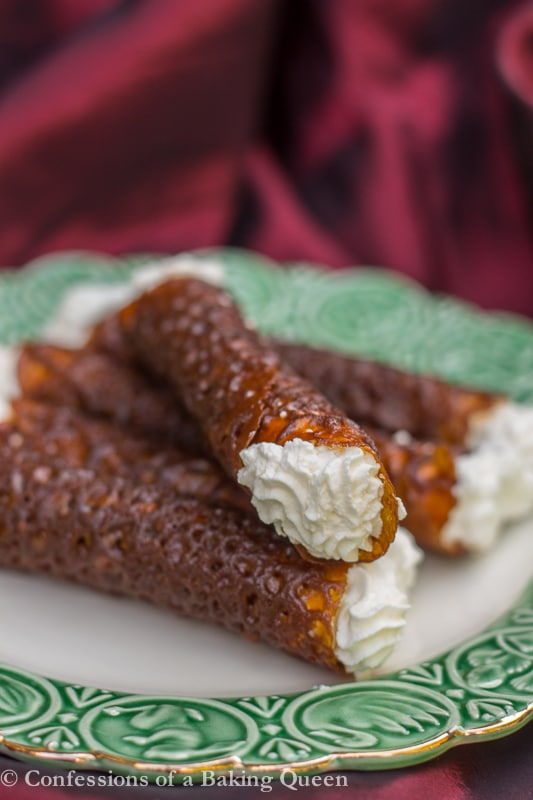 Brandy Snaps on top of each other on white plate with green rim