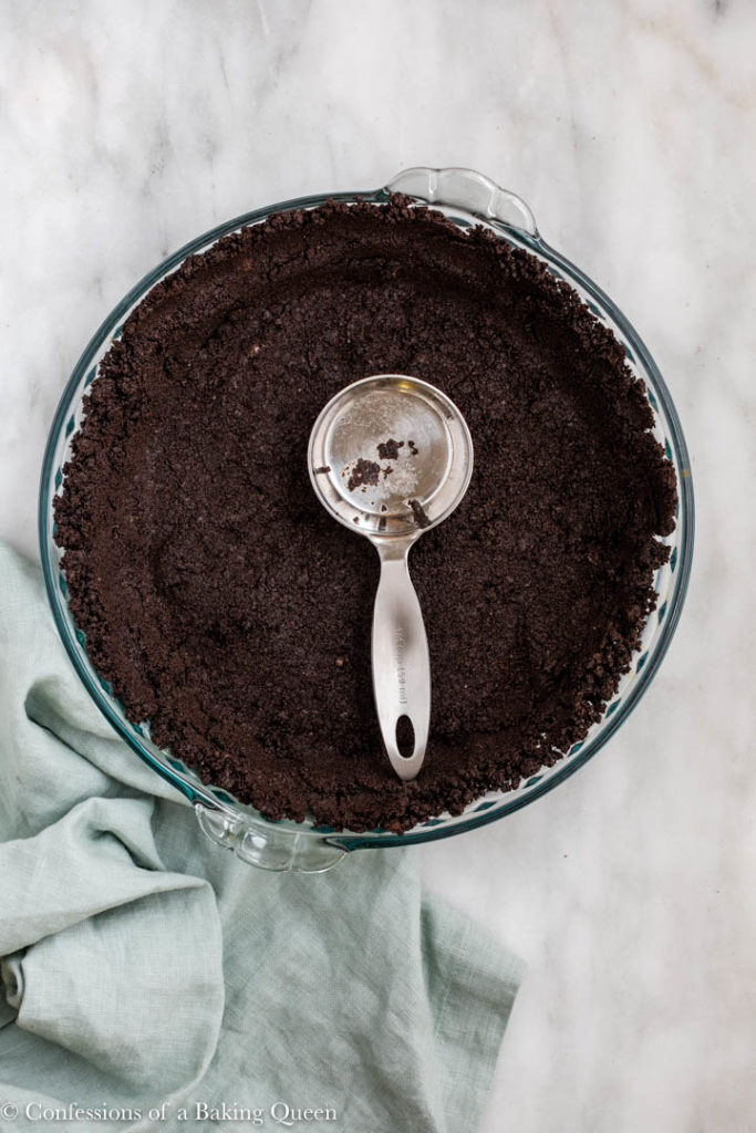 oreo crust pressed down with a metal measuring cup in a glass pie dish