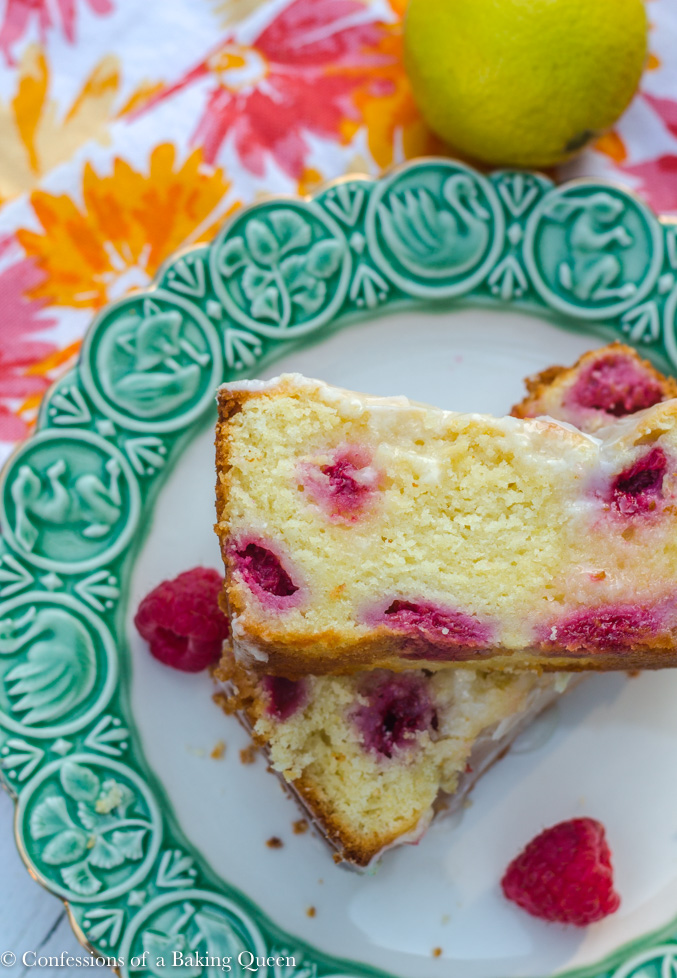 raspberry lemon loaf cake sliced and stacked on a white and green plate with raspberries