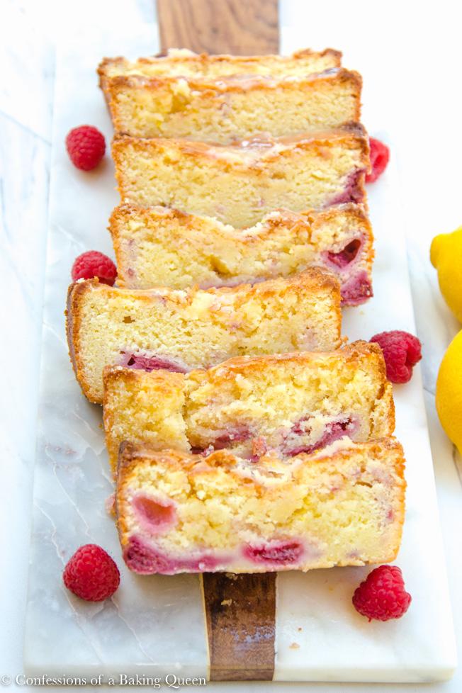 raspberry lemon loaf cake sliced served on a white plate with raspberries