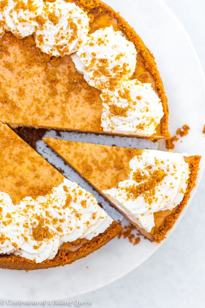 pumpkin cheesecake with a slice being taken out on a white marble cake stand