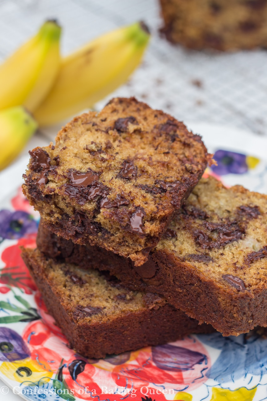 Chocolate Chip Banana Bread Recipe baked and pieces stacked on top of each other on a colorful plate with bananas in the background