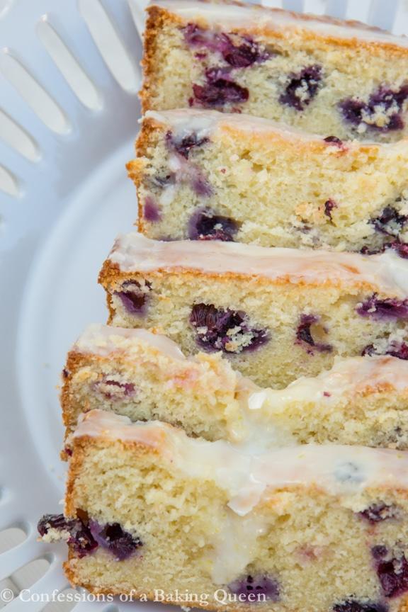sliced lemon blueberry loaf cake on a white plate
