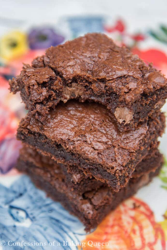 Chewy Fudgy Brownies stacked on top of each other on a colorful plate