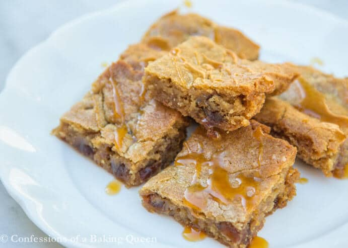 Sticky Toffee Pudding Blondies baked and stacked on top of each other on a white plate