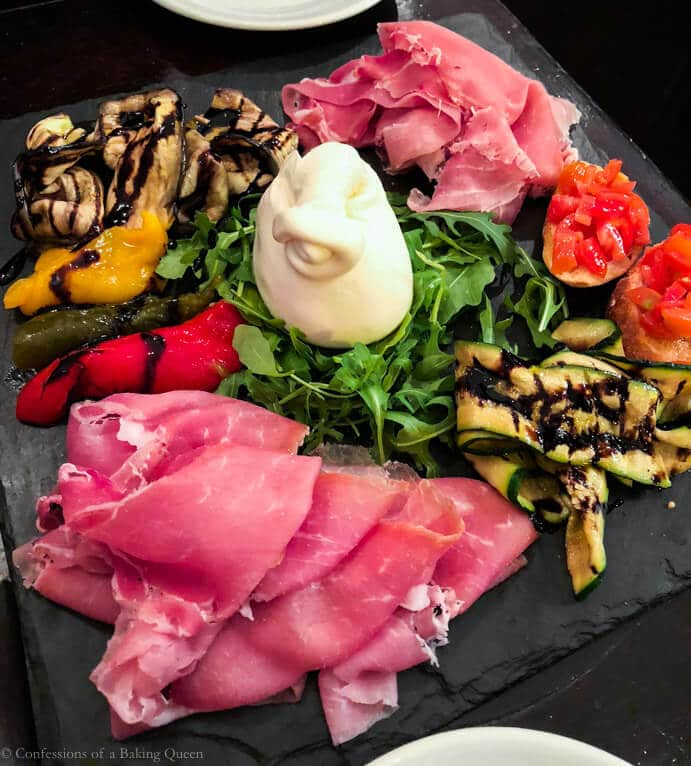 meat cheeses and veggies on a black slate board paris eats