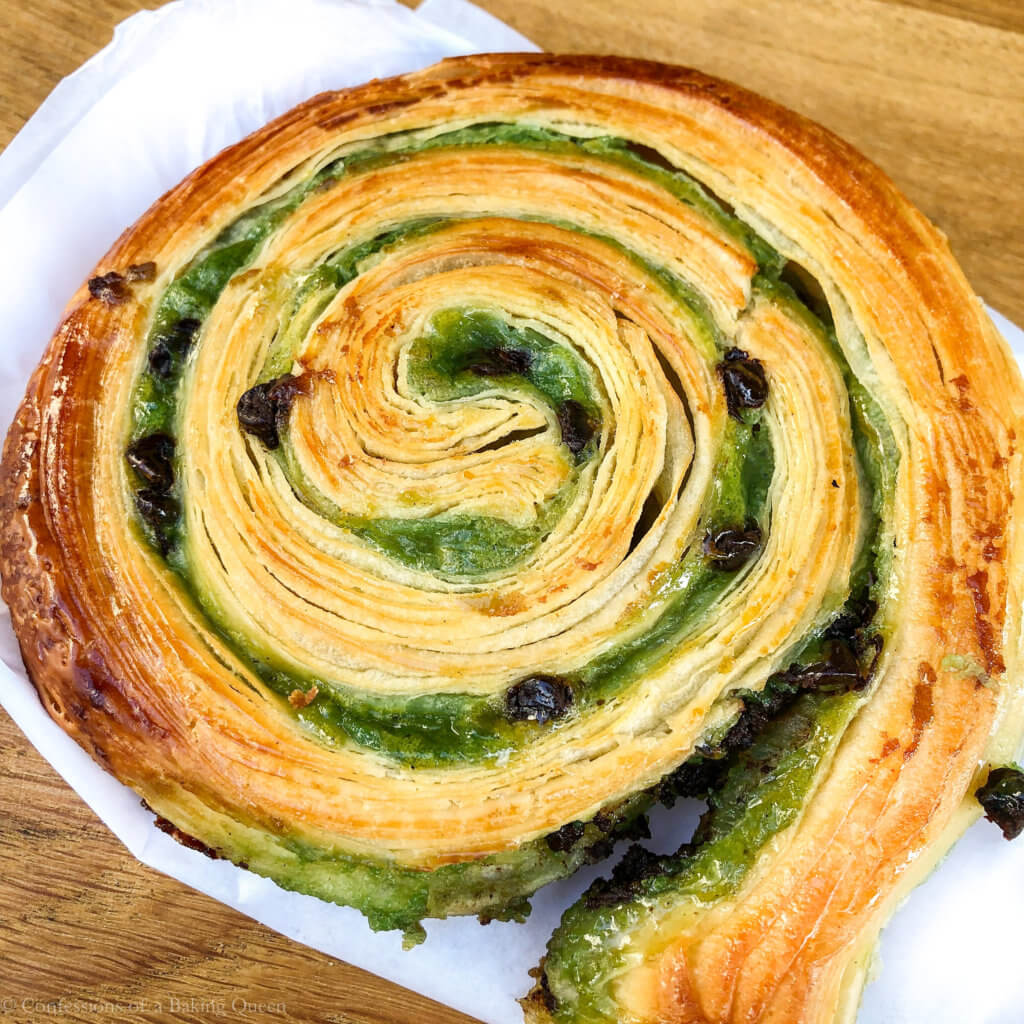 paris eats pastry snail showing the green filling with chocolate chips on a wood board