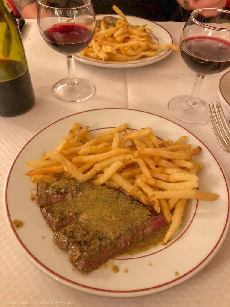steak frites on a white tablecloth with wine glasses paris eats