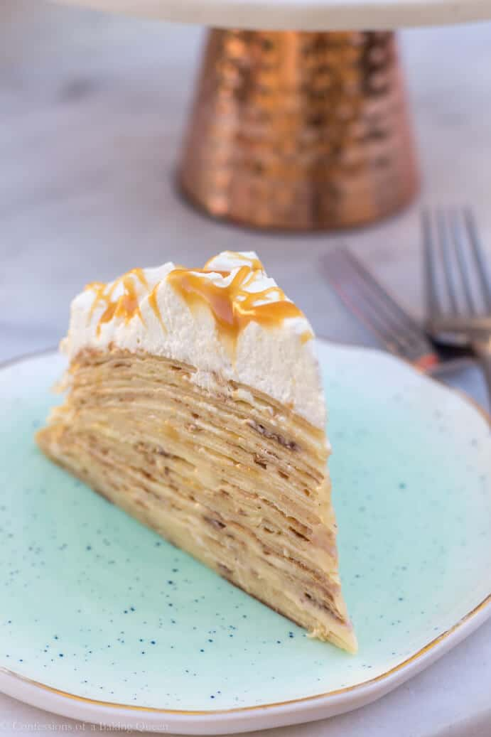 up close view of salted caramel crepe cake slice on a blue plate with forks in background