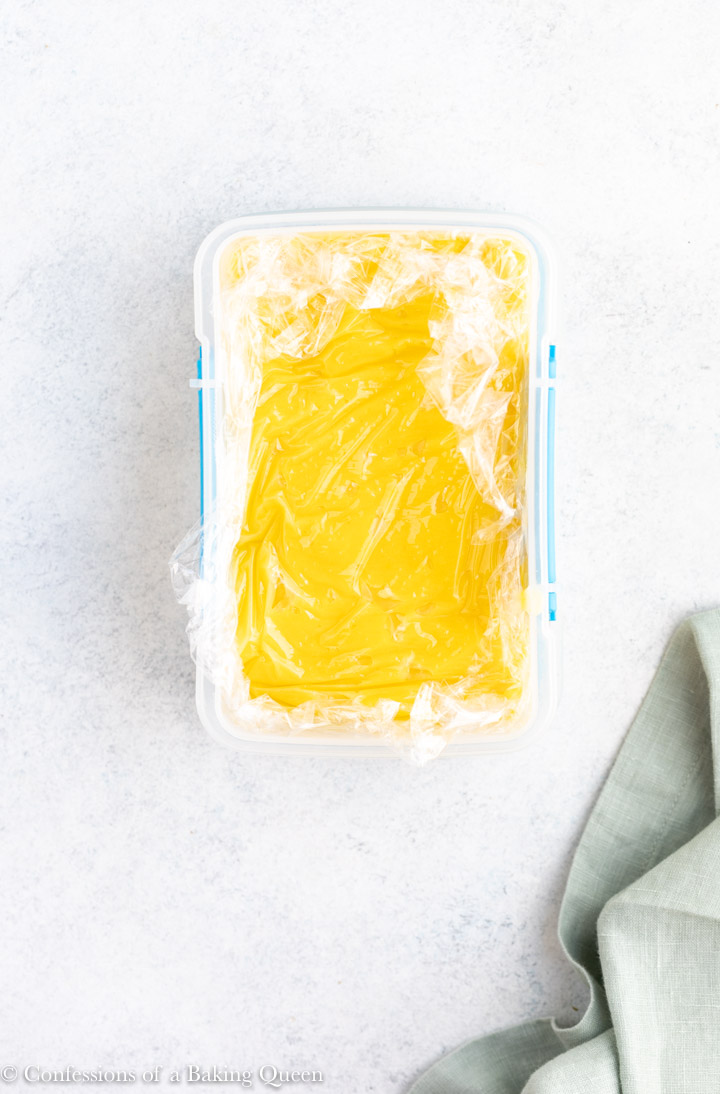 lemon curd cooling in a plastic container with plastic wrap on the top