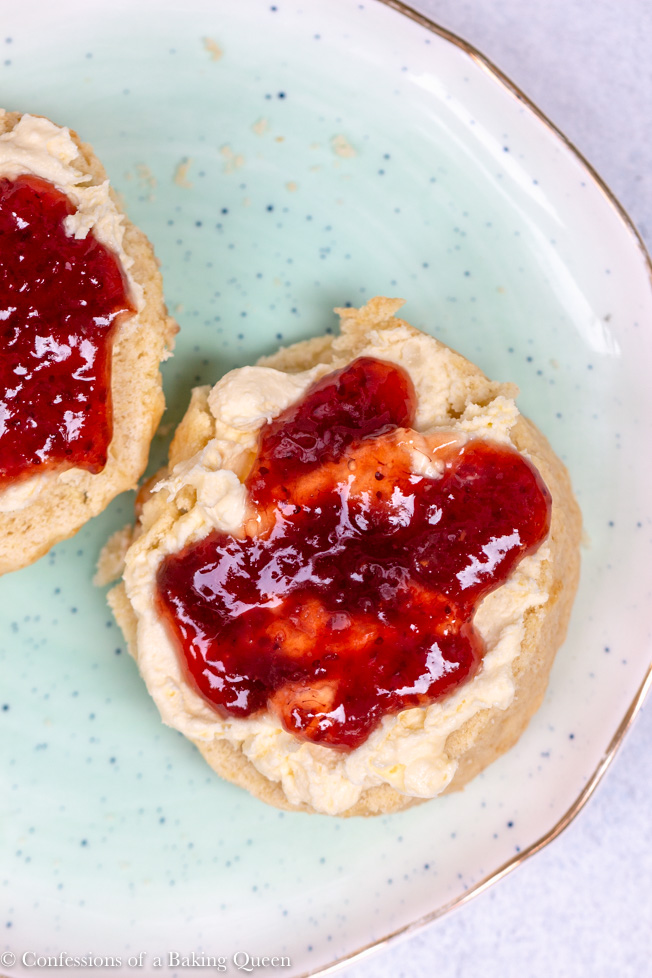 overhead shot of english scone with clotted cream and jam on