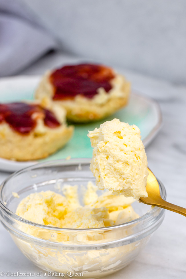 clotted cream in a clear bowl with a gold spoon holding a scoop with scones in the background