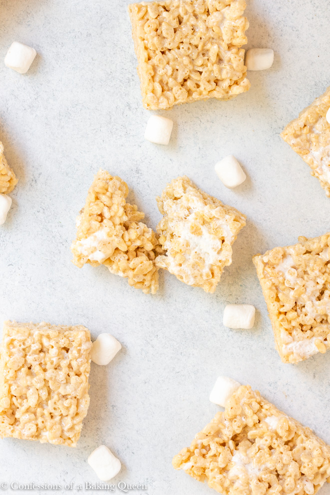 brown butter rice krispies cut up and set on a white background with mini marshmallows scattered about