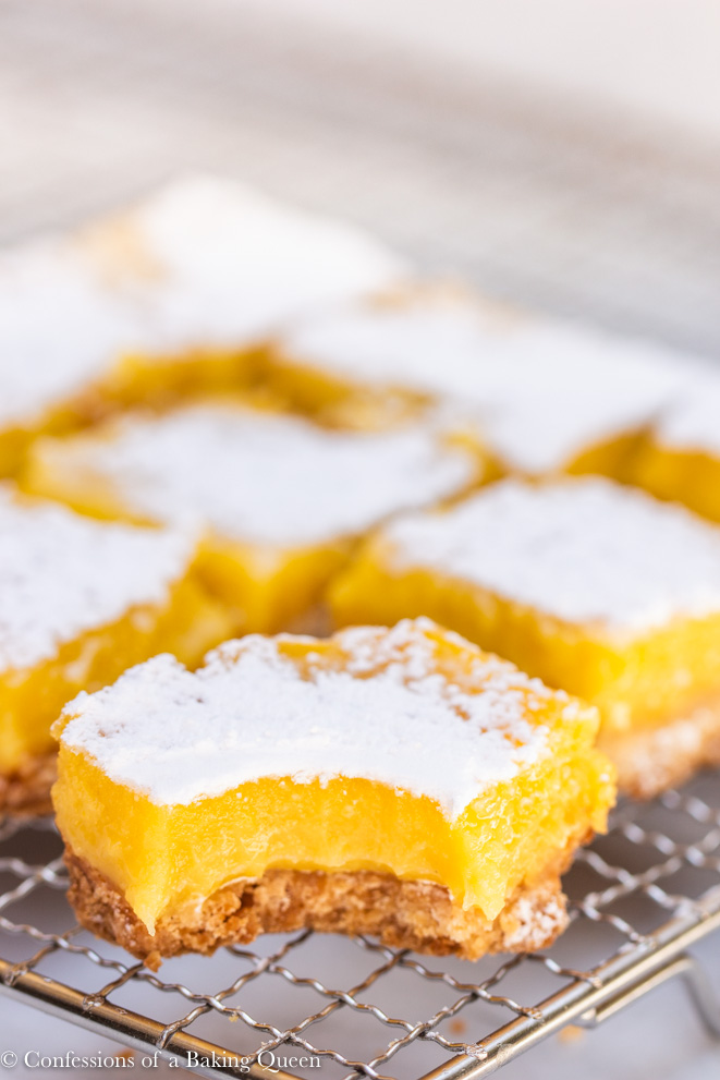 lemon bar with a bite missing on a wire rack with more lemon bars behind