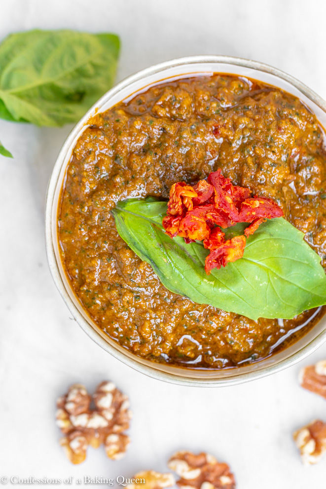 sun-dried tomato pesto recipe served in a small bowl on marble top with walnuts and basil leaves