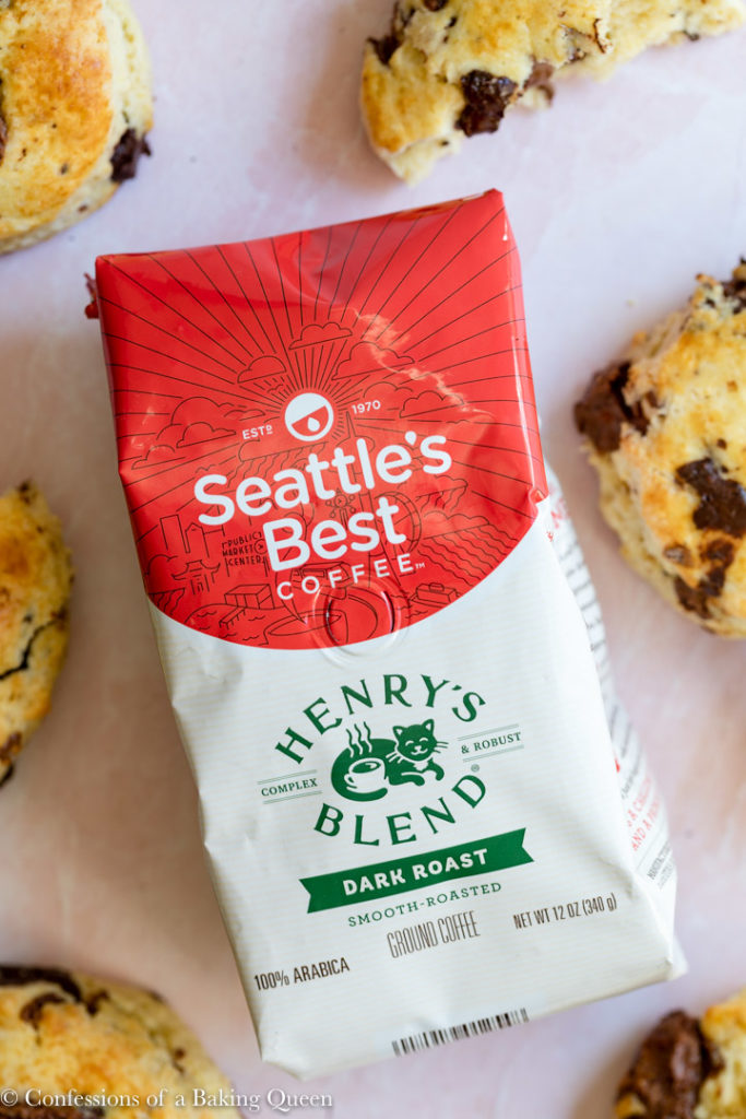 seattles best henrys coffee bag on a pink surface with chocolate chip scones surrounding it