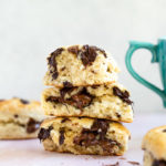 chocolate chunk scones stacked on top of each other on a pink surface