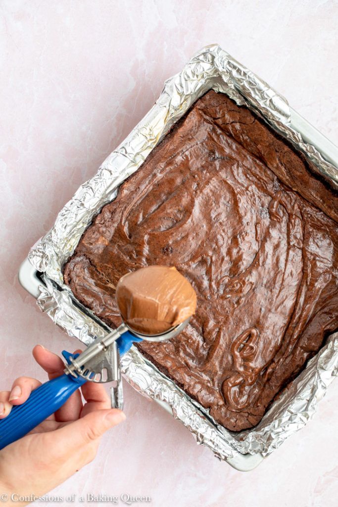 hand holding cookie scoop full of chocolate cheesecake batter to place on top of brownies