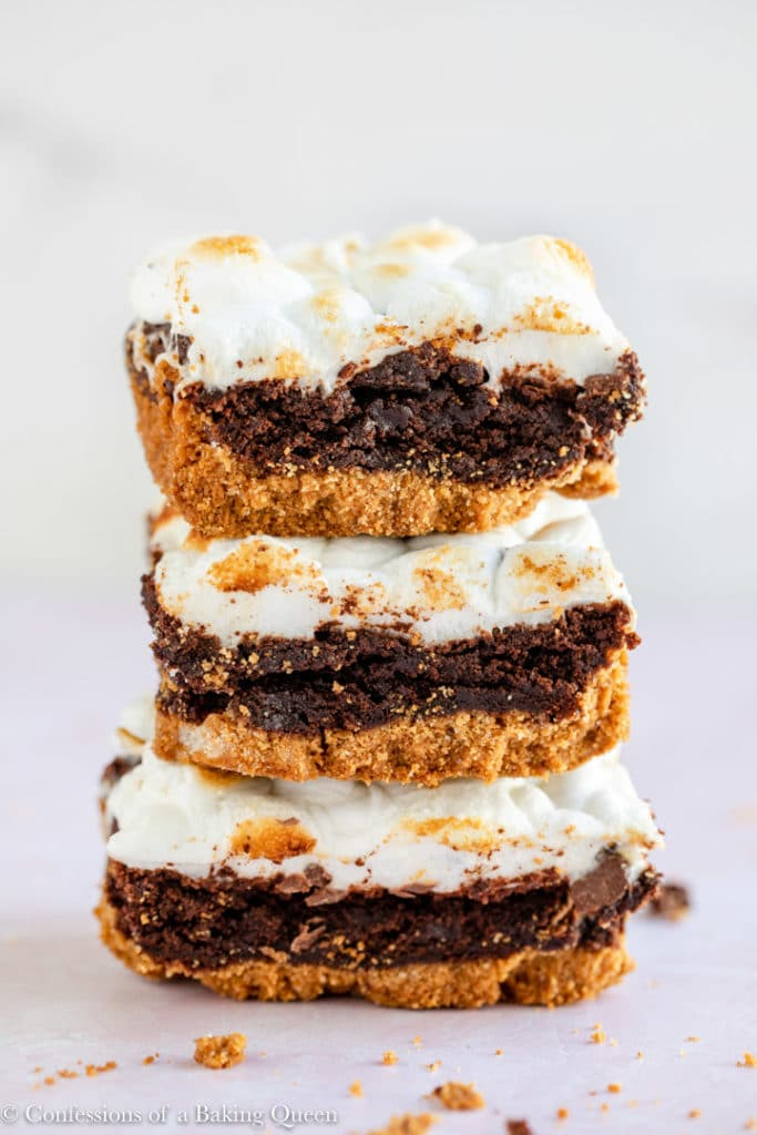 three s'mores brownies stacked on top of each other on a light pink surface