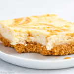 close up of a dulce de leche cheesecake bar on a white plate