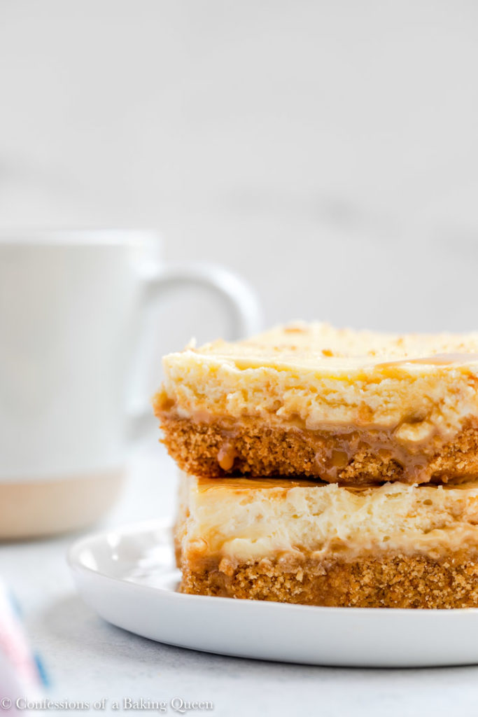 two dulce de leche cheesecake bars on a small white plate