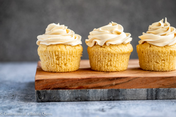 three baileys cupcakes on a wood and marble board